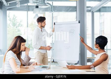 Junger Geschäftsmann, Präsentation, Kolleginnen und Kollegen auf der Sitzung im Büro - Stockfoto