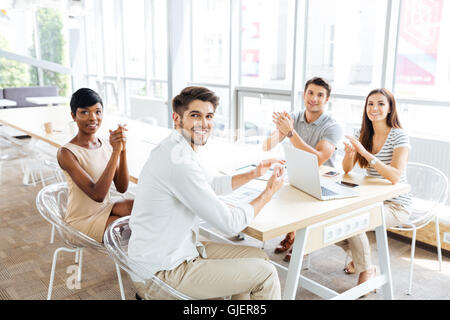 Gruppe von fröhlichen jungen Geschäftsleute sitzen und Händeklatschen während der Präsentation im Büro - Stockfoto