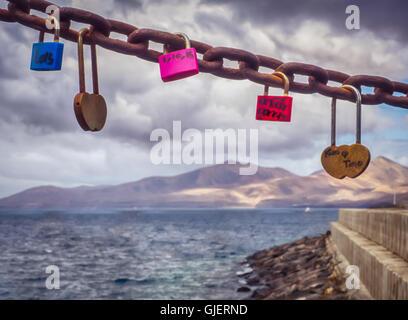 Vorhängeschlösser mit Liebhaber Namen und Initialen, befestigt an einer Kette an der Strandpromenade von Playa Blanca, - Stockfoto