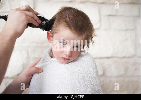 Junge, eine Summen Haare schneiden von seinem Vater - Stockfoto
