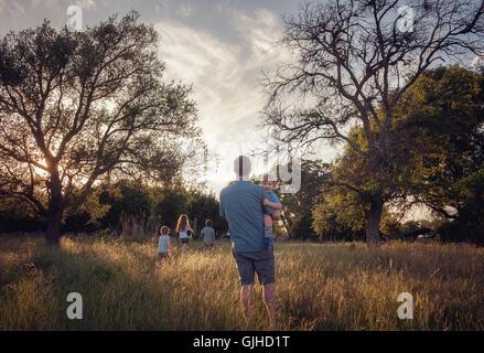Vater und seinen vier Kindern zu Fuß in ländlichen Landschaft an der Dämmerung, Texas, Amerika, USA - Stockfoto