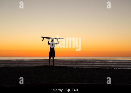 Silhouette des Menschen stehen am Strand bei Sonnenaufgang Holding Longboard über seinem Kopf, San Diego, Kalifornien, - Stockfoto