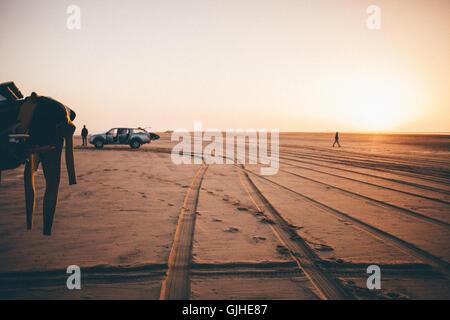 Silhouette der beiden Surfer und Autos am Strand bei Sonnenaufgang, namibia - Stockfoto