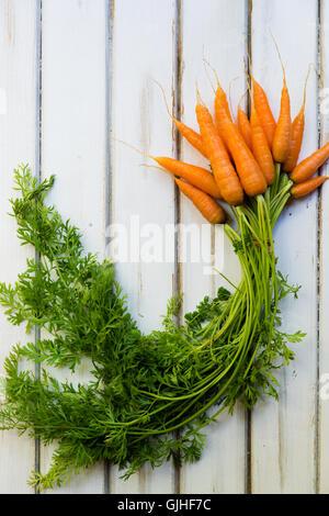 Reihe von Karotten auf Holztisch - Stockfoto
