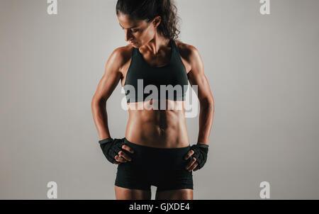 Starke junge Frau, die mit ihren Händen auf den Hüften zeigen ihre muskulösen abs passen, beschnittenen Nahaufnahme - Stockfoto