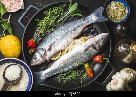 Zutaten für Cookig gesunden Fisch zum Abendessen. Rohe ungekochte Wolfsbarsch Fisch mit Reis, Zitrone, Kräuter und - Stockfoto