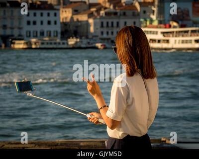 Junge asiatische Erwachsene weibliche Touristen nehmen ein Selbstporträt mit einem Selfie-Stick; machte das V-Zeichen - Stockfoto