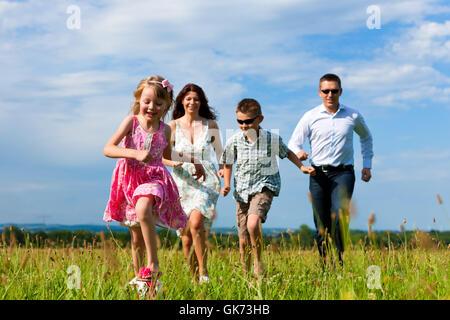 glückliche Familie auf einer Wiese im Sommer - Stockfoto