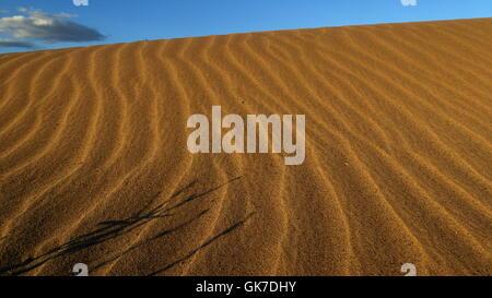 Düne mit Sand Wellenmuster in der Wüste mit blauen Himmel und Wolken - Stockfoto