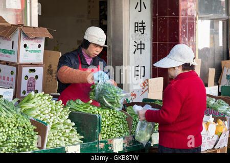 San Francisco, Kalifornien: Ladenbesitzer verkaufen Gai lan (chinesische Brokkoli) an einen Kunden entlang der Stockton - Stockfoto