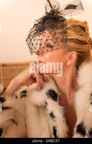 Blonde Frau in schwarz / weiß Kunstpelz Mantel - Stockfoto