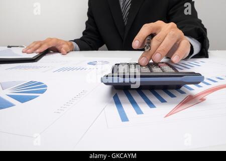 Asian Business-Mann, die Verwendung eines Taschenrechners, die Zahlen zu berechnen - Stockfoto