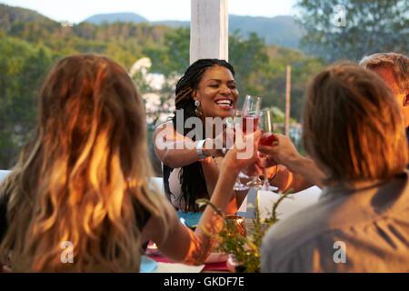 Paare beim Abendessen auf der Terrasse, über Schulter Blick Toasten - Stockfoto