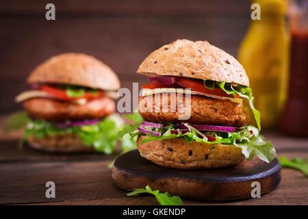 Big Sandwich - Hamburger mit saftige Hähnchen Burger, Käse, Tomaten und roten Zwiebeln auf hölzernen Hintergrund - Stockfoto