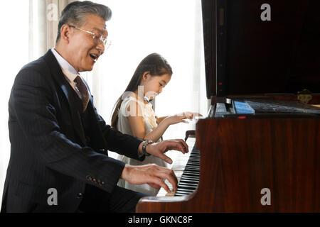 Großvater und Enkelin spielen Klavier zusammen - Stockfoto