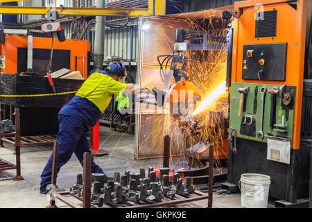 """Arbeiter, Schleifen oder Schneiden entfernt werfen Metallkomponenten aus seinem """"Casting"""" Baum. - Stockfoto"""