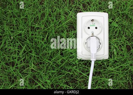 elektrische Steckdose auf einem grünen Rasen-Hintergrund - Stockfoto