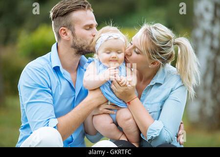 Porträt von Eltern küssen ihr Babymädchen - Stockfoto