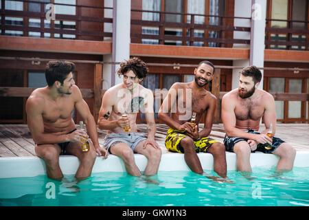 Gruppe von gutaussehenden jungen Männer sitzen und trinken Bier in der Nähe von Schwimmbad - Stockfoto