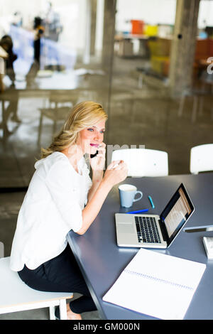 Junge Managerin arbeiten an ihrem Schreibtisch im Büro nehmen einen Anruf auf ihrem Mobiltelefon - Stockfoto