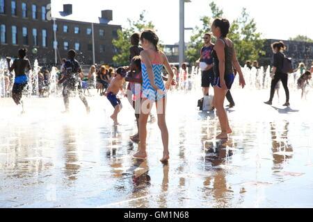 Kinder spielen in den Wasserbrunnen in Granary Square, auf ein heißes, Sommertag, bei Kings Cross, Nord London, - Stockfoto