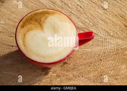 Ein schönen Cappuccino in der goldenen Sonne saßen auf einem natürlichen Stück Holz. - Stockfoto