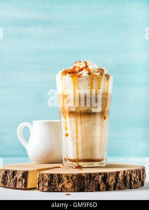 Latte Macchiato mit Schlagsahne Sahne-Karamell-Sauce im Longdrinkglas auf Runde hölzerne Portion Brett über blau - Stockfoto