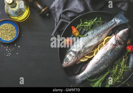 Zutaten für Cookig gesunden Fisch zum Abendessen. Rohe ungekochte Seebarsch mit Olivenöl, Kräutern und Gewürzen - Stockfoto