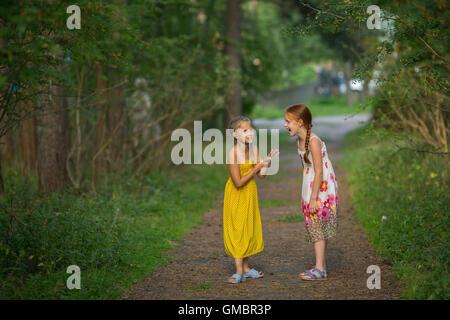 Zwei kleine Mädchen emotional sprechen im Park. - Stockfoto