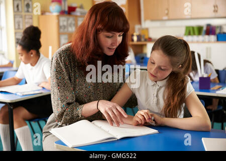 Lehrer hilft einem Mädchen an ihrem Schreibtisch, beide auf der Suche nach unten Nahaufnahme - Stockfoto
