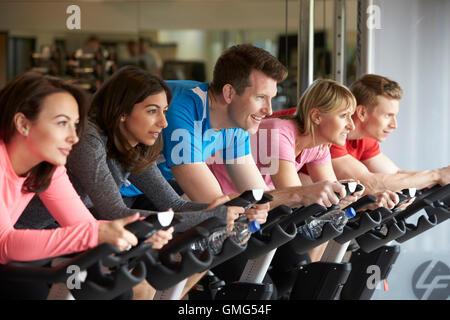 Seitenansicht von einem Spinning Kurs auf Ergometern in einem Fitnessstudio - Stockfoto