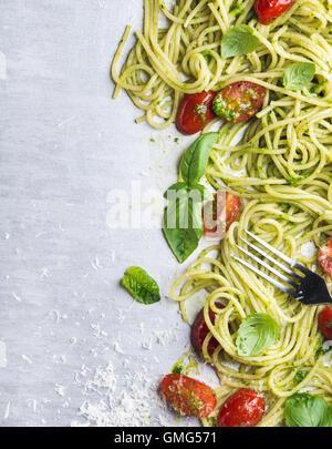 Spaghetti mit Pesto-Sauce, gebratenen Kirschtomaten, frischem Basilikum und Parmesan-Käse auf Stahl Hintergrund - Stockfoto