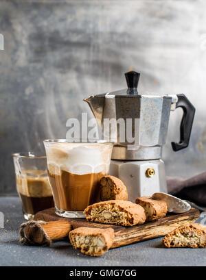 Glas Latte Kaffee auf rustikalem Holzbrett, Cantucci Kekse und italienischen Moka Stahltopf, grauen Hintergrund