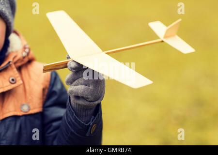 Nahaufnahme eines kleinen Jungen Spielzeug Flugzeug draußen halten - Stockfoto