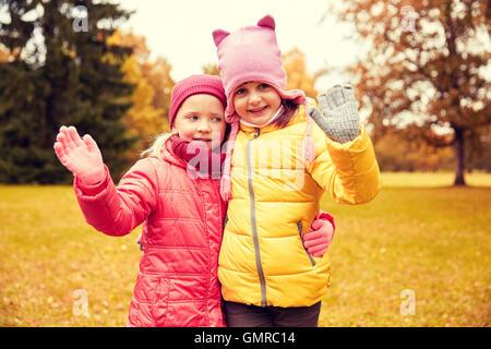 zwei glückliche kleine Mädchen winken Hand im Herbst park - Stockfoto