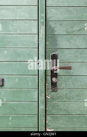 Eine grüne Holztür mit einem abgenutzten Metallgriff und Längsstreifen. - Stockfoto