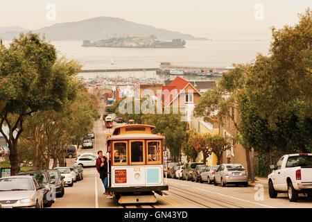 Eine Seilbahn kriecht oben Hyde Street, einer der San Francisco viele steile Straßen mit Alcatraz Island im Hintergrund. - Stockfoto