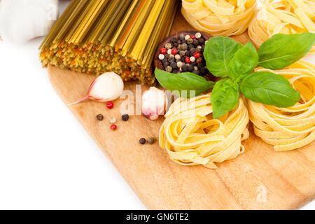 Italienische Nudeln Fettuccine nisten mit frischem Basilikum auf weißem Hintergrund - Stockfoto