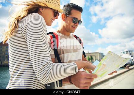 Niedrigen Winkel Ansicht eines touristisch attraktiven jungen Paares Blick auf eine Karte im Freien in der Sommersonne - Stockfoto