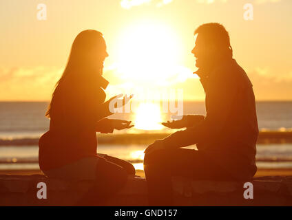 Seitenansicht der zusammen reden bei Sonnenaufgang am Strand mit der Sonne in der Mitte ein paar silhouette - Stockfoto
