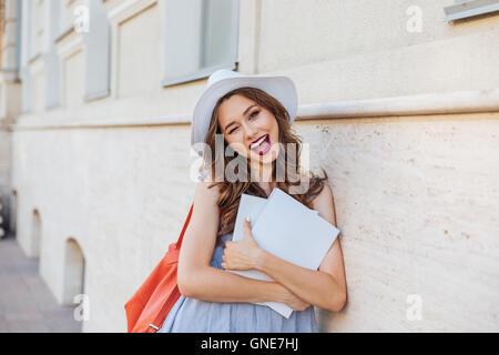Fröhlich, hübsche junge Frau mit Hut mit leeren überdachte Zeitschriften zwinkert und Daumen nach oben zeigen