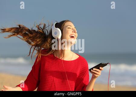 Glückliches Mädchen rot bunt Trikot tanzen singen und hören Musik auf Linie mit Kopfhörern über ein Smartphone - Stockfoto