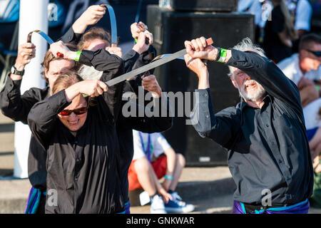 Englisch Volkstänzer, der Hawksword Rapper Morris Men Tanz mit der flachen Klinge Messer auf einem freien Holzterrasse. - Stockfoto