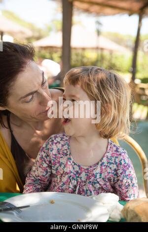 Brünette Frau Überraschung Gesicht mit kleinen Kind zwei Jahre alt lachenden Ausdruck sitzen an den Beinen außen - Stockfoto