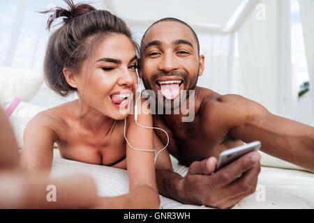 Fröhliche Brautpaar Selfie zu machen und zeigt Zungen beim hören von Musik am Strand - Stockfoto