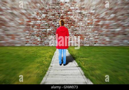 Junge Frau stand vor einer riesigen Wand - Stockfoto