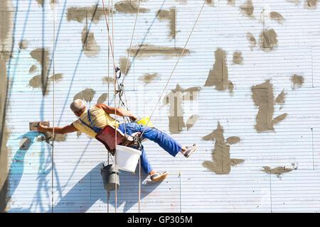 Ein Arbeiter auf einer Wärme- und Gebäudeisolierung arbeitet hängt an Seilen an der Wand des Gebäudes. - Stockfoto