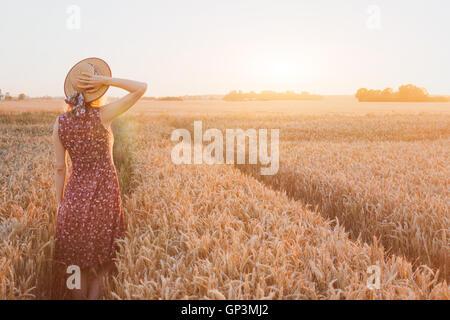 Sommer glückliche junge Frau im Weizenfeld mit Sonnenuntergang, Tagtraum, schönen Hintergrund mit Platz für text