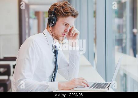 Geschäftsmann in Kopfhörer arbeiten mit Laptop im modernen Café-Interieur - Stockfoto