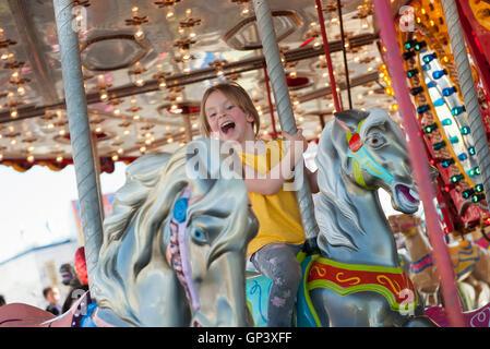 Kleines Mädchen reiten auf Karussell - Stockfoto